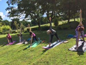 Trikonasana under the trees on a Diversity Yoga day retreat in Ascot