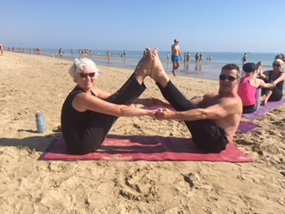 Partner Yoga Navasana on the beach - Diversity Yoga retreat Italy